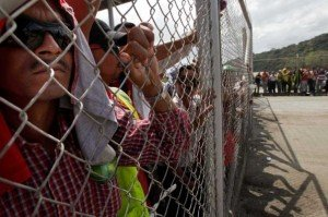 Panama Canal workers look on from behind a fence as strike enters day number 2