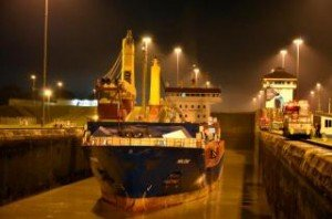 Conatainer ship is illuminated as it passes through the Panama Canal at night.