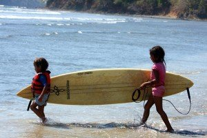 Two young children carry a surfboard to the water in Santa Catalina, Panama