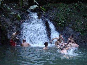 Tour members enjoy splashing in this waterfall during the Panama Canal Kayak Tour